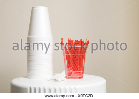 Polystyrene cups and plastic stirrers on top of coffee machine - Stock Photo