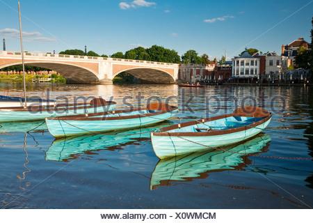 Moored rowing boats on the River Thames at Hampton Bridge, Surrey, Uk - Stock Photo