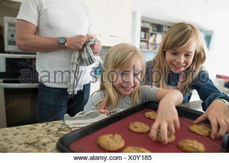 Excited girls reaching for fresh baked cookies in kitchen - Stock Photo