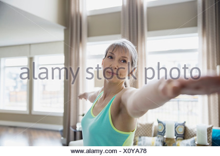 Woman practicing yoga in living room - Stock Photo