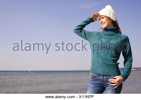 Young woman on the beach looking into distance - Stock Photo