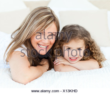 Little girl with her mother looking at the camera while lying on a bed - Stock Photo