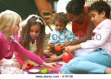Mother and four children playing picnics at garden birthday party - Stock Photo