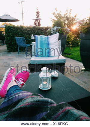 Young woman sitting relaxing in her garden with legs on table - Stock Photo