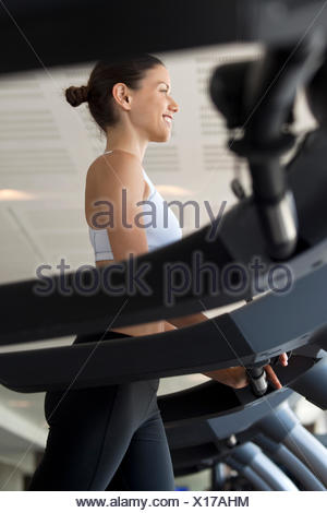 Woman on exercise machine at gym - Stock Photo