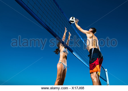 Two beach volleyball players blocking at net - Stock Photo