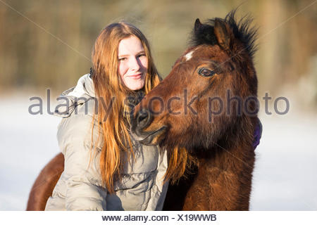 Welsh Pony (Section B). Girl cuddling up to a bay horse on a snowy pasture. Germany - Stock Photo
