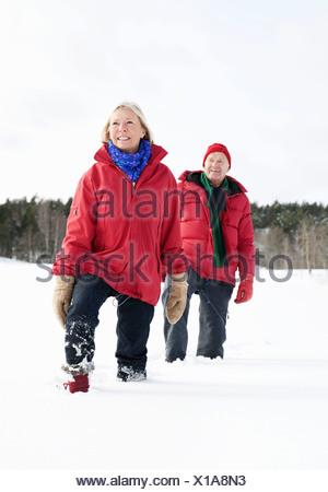 Twp seniors walking through the snow - Stock Photo
