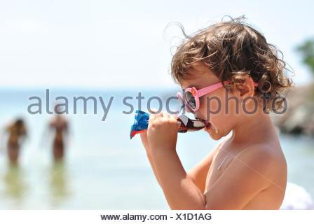 little girl eating ice cream on the beach of sea - Stock Photo