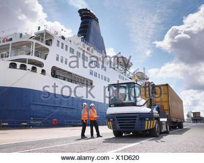 Port workers on dock side beside ship - Stock Photo