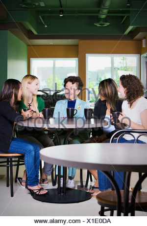 Older woman talking to group of young friends - Stock Photo
