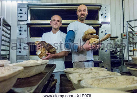 Bakers holding freshly-made bread - Stock Photo