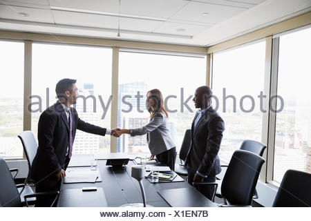 Business people handshaking in urban conference room meeting - Stock Photo