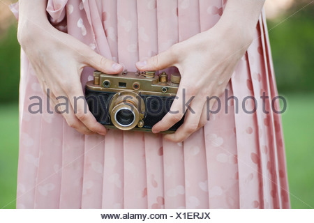 Russia, Voronezh, midsection of woman holding old camera - Stock Photo