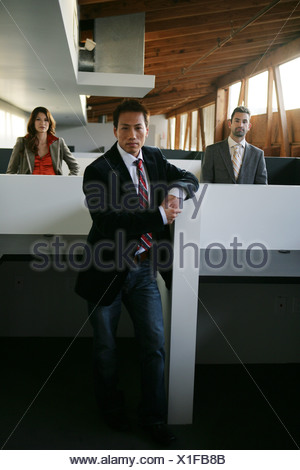 Three business people standing among cubicles - Stock Photo