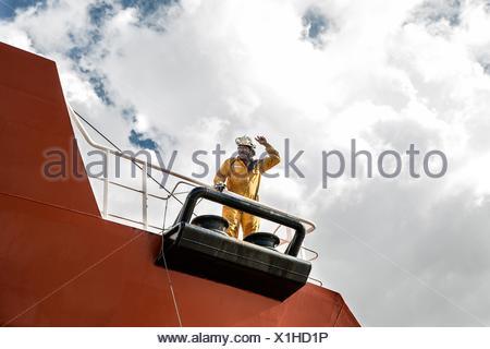 Worker mooring oil tanker on deck making hand gesture - Stock Photo