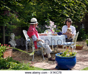 Couple sitting at table on patio in summer garden - Stock Photo