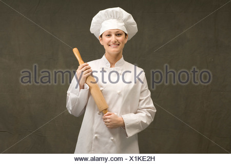 Chef holding rolling pin - Stock Photo