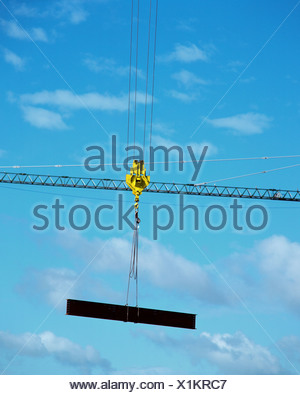 Industrial crane holding a girder - Stock Photo