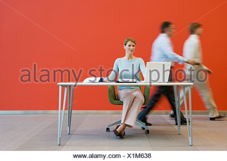 Men walking past woman at desk - Stock Photo