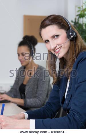 Eine junge Büroangestellte mit Headset schreibt in ein Dokument. Eine weitere Frau mit Headset befindet sich im Hintergrund und arbeitet am Notebook (unscharf). - Stock Photo