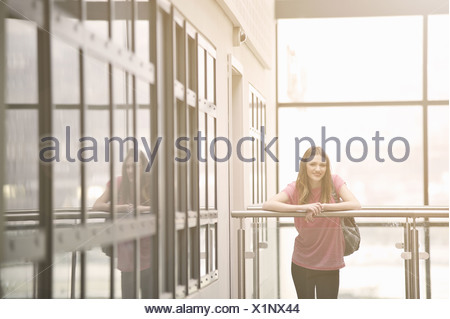 Young woman leaning on railing - Stock Photo