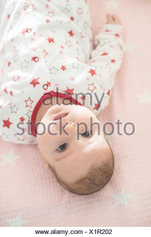 Baby girl lying in a cot - Stock Photo