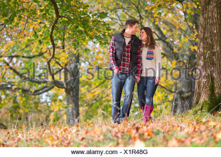 Happy couple, walking through autumnal forest, holding hands - Stock Photo