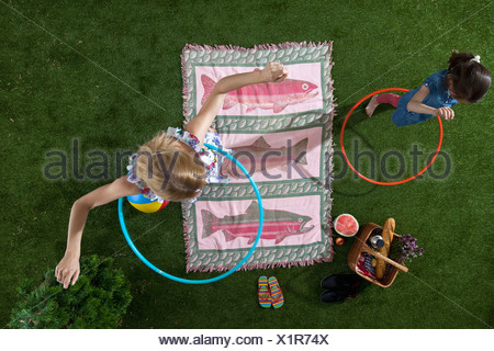 A mother and daughter using hula hoops at a picnic in the park, overhead view - Stock Photo