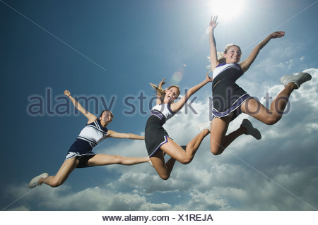 Three cheerleaders jumping - Stock Photo