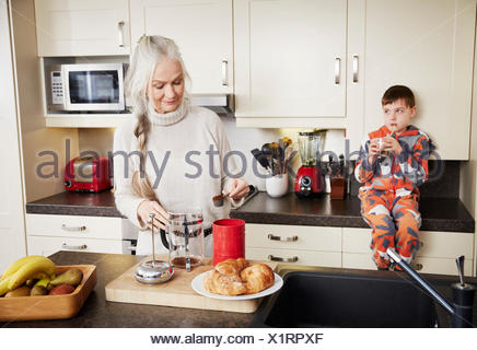 Grandmother making coffee, grandson sitting on kitchen counter - Stock Photo