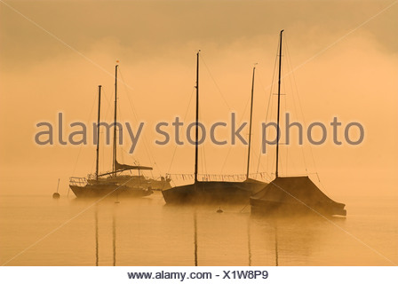 Morning fog above Lake Starnberg and silhouettes of boats at Seeshaupt, Bavaria, Germany, Europe - Stock Photo