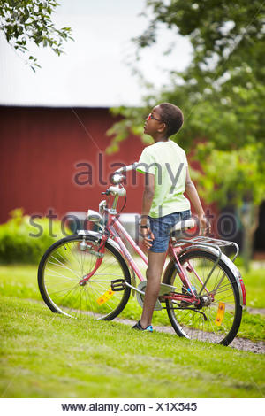 Sweden, Vastra Gotaland, Gullspang, Runnas, Boy (8-9) on bike - Stock Photo
