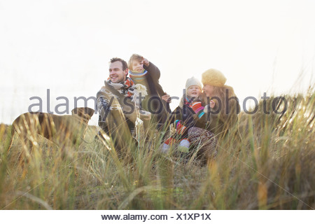 Mid adult couple in sand dunes with their son, daughter and dog - Stock Photo
