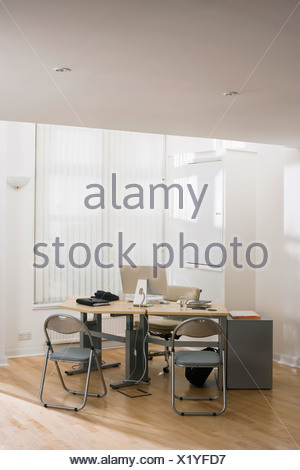 Flat screen computer monitor on desk in empty office two folding chairs in front of desk - Stock Photo