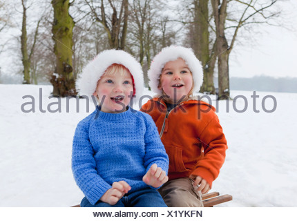 Two boys wearing fluffy hats in the snow - Stock Photo