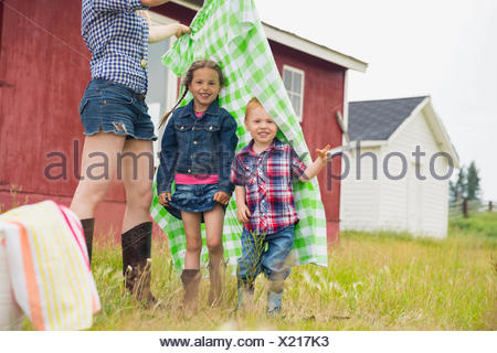 Portrait of brother and sister under picnic blanket - Stock Photo