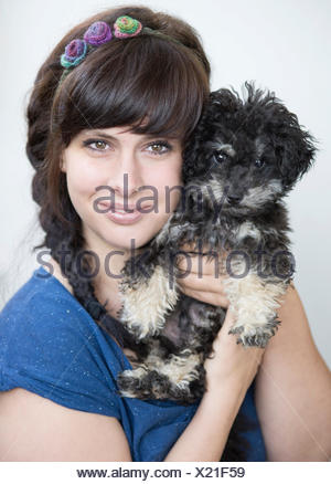 Young woman holding a Toy Poodle, or Teacup Poodle, black and tan, Austria - Stock Photo