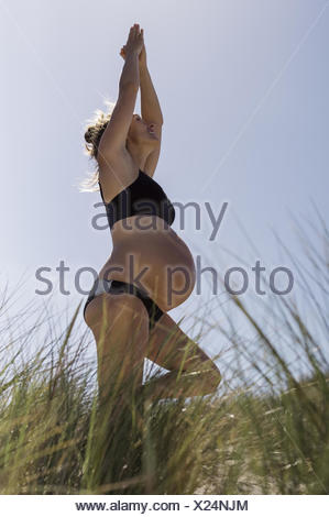 A pregnant woman standing in a yoga pose in the sunshine. - Stock Photo