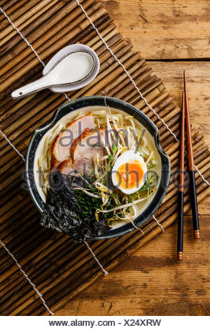 Udon noodle with boiled pork, wheat germ and egg on wooden background - Stock Photo
