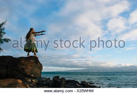 Woman hula dancing on top of coastal rocks wearing traditional costume, Maui, Hawaii, USA - Stock Photo