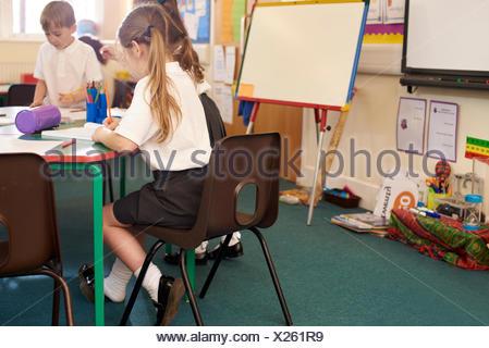 Pupils Working At Desks In Elementary School Classroom - Stock Photo