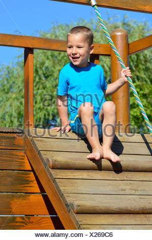 little boy sitting on a climbing tower - Stock Photo