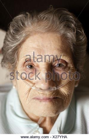 Elderly woman using a nasal oxygen cannula - Stock Photo