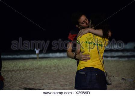 Young couple in love at Copacabana beach at night, Rio de Janeiro, Brazil. - Stock Photo