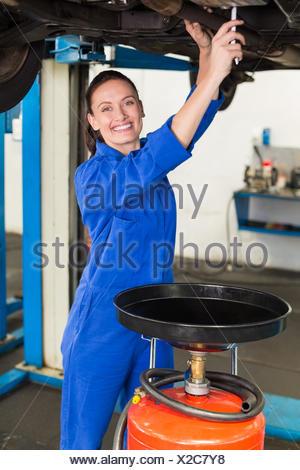 Mechanic adjusting something under car - Stock Photo