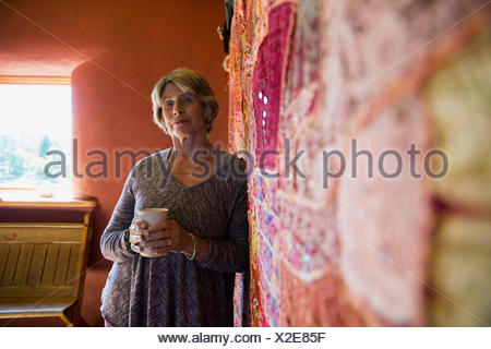 Portrait confident senior woman drinking coffee at tapestry - Stock Photo