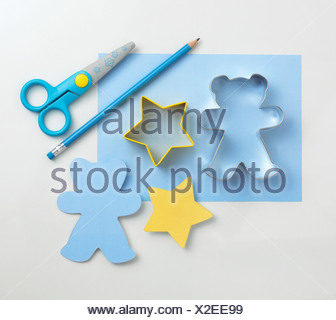 Cookie cutters, paper, pencil and scissors on white background, close-up - Stock Photo