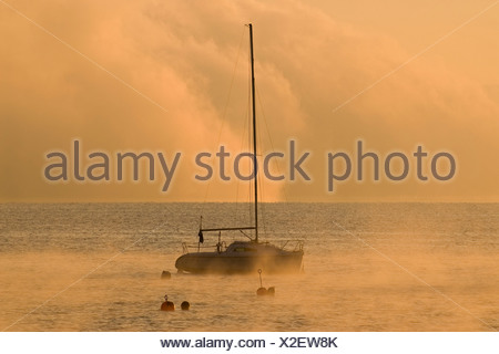 Sailing boat and low morning fog over Ammersee lake at Utting, Bavaria, Germany, Europe - Stock Photo