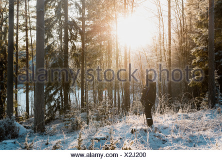 Mature man standing in snow covered forest - Stock Photo